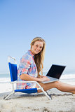 Pretty blonde sitting on beach using her laptop smiling at camera