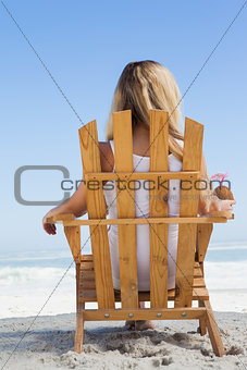 Pretty blonde sitting in deck chair holding coconut drink