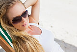 Gorgeous blonde in sunglasses sitting at the beach
