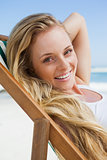 Gorgeous blonde sitting at the beach smiling at camera