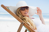 Gorgeous blonde sitting at the beach wearing sunhat and sunglasses