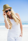 Stylish blonde smiling at camera on the beach