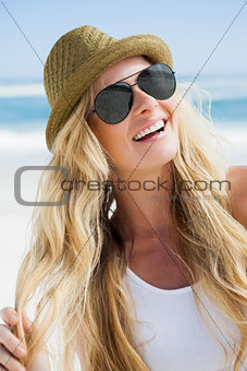 Stylish blonde smiling on the beach