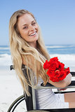 Wheelchair bound blonde smiling at the camera on the beach holding roses