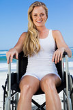 Wheelchair bound blonde sitting on the beach smiling at camera