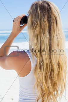 Blonde looking to the ocean through binoculars