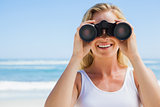 Blonde looking through binoculars on the beach