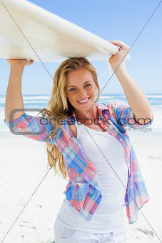 Blonde surfer holding her board smiling at camera