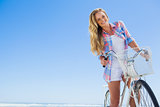 Pretty blonde on a bike ride at the beach smiling at camera