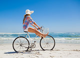 Pretty carefree blonde on a bike ride at the beach