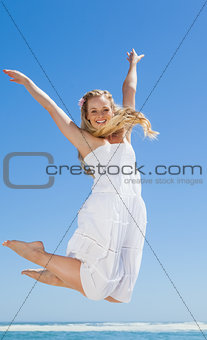 Pretty carefree blonde jumping and smiling at camera on the beach