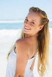 Pretty carefree blonde smiling at camera on the beach