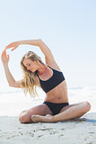 Fit blonde sitting in yoga pose on the beach