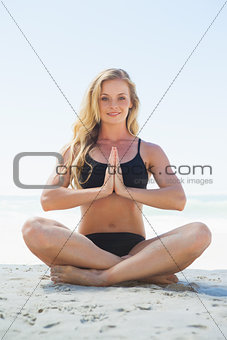 Fit blonde sitting in lotus pose on the beach