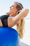 Fit blonde doing sit ups on exercise ball at the beach