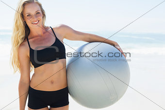 Fit blonde holding exercise ball at the beach smiling at camera
