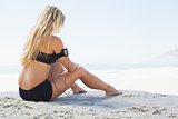 Fit blonde sitting in on the beach taking a break
