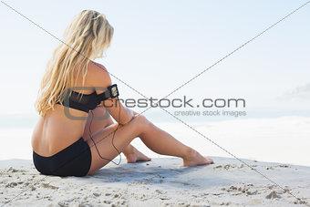 Fit blonde sitting in on the beach taking a break