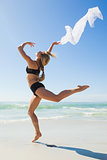 Fit blonde jumping gracefully with scarf on the beach
