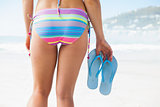 Lower half of fit woman holding flip flops on beach