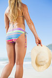 Fit woman holding sunhat on beach