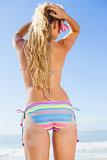 Rear view of fit woman in bikini on beach