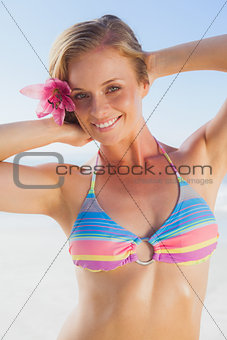 Gorgeous blonde in bikini smiling at camera on the beach