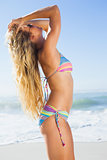 Gorgeous blonde in bikini and sunglasses on the beach posing