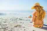 Gorgeous woman sitting on the beach in sunhat applying suncream