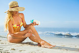 Gorgeous woman sitting on the beach in sunhat applying suncream