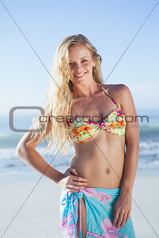 Pretty blonde in bikini and sarong smiling at camera on the beach