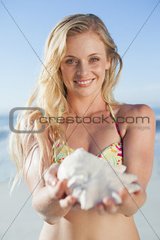 Pretty blonde in bikini holding conch on the beach