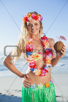 Gorgeous blonde in garland holding coconut drink on the beach