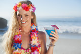 Gorgeous blonde in garland holding cocktail on the beach