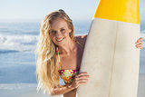 Gorgeous blonde surfer in bikini holding her board