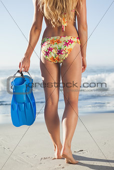 Woman holding flippers walking towards the sea