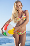 Gorgeous blonde in floral bikini holding beach ball