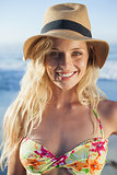 Gorgeous blonde in straw hat smiling at camera on beach