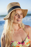 Gorgeous blonde in straw hat smiling on beach