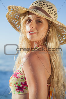 Gorgeous blonde in straw hat and bikini smiling at camera on beach