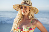 Gorgeous blonde in straw hat and bikini smiling on beach