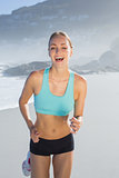 Fit woman smiling and jogging on the beach