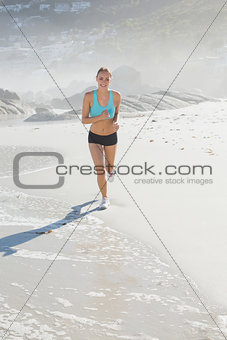 Fit woman jogging on the beach smiling at camera