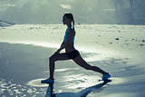 Fit woman doing lunges on the beach