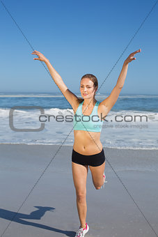 Fit woman stretching on the beach