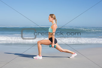 Fit woman doing weighted lunges on the beach