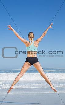 Fit woman jumping on the beach with arms out