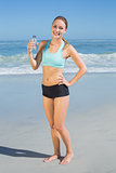 Fit woman standing on the beach holding water bottle