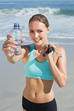 Fit woman standing on the beach holding water bottle and skipping rope