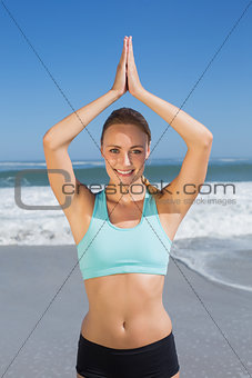 Fit woman meditating on the beach